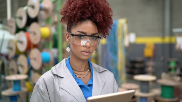 Portrait of woman using tablet working in industry Portrait of woman using tablet working in industry production line worker stock videos & royalty-free footage