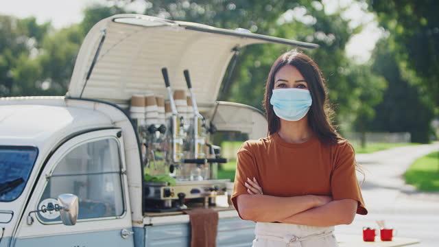 portret kobiety noszącej maskę na twarz podczas pandemii zdrowia, prowadzącej niezależną mobilną kawiarnię stojącą na zewnątrz obok składanych ramion vana i patrzącą na kamerę - nakręcaną w zwolnionym tempie - barista filmów i materiałów b-roll
