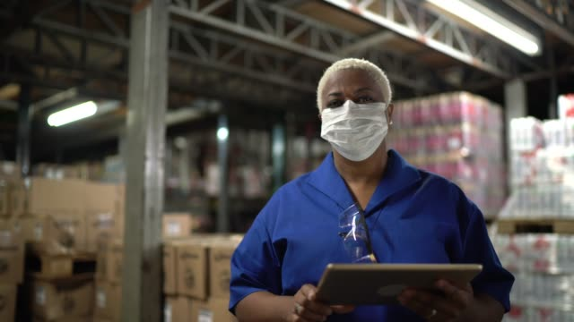 Portrait of woman wearing face mask using digital tablet - working in warehouse / industry video