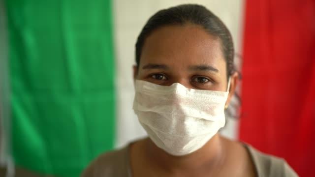 ritratto di donna con maschera facciale e bandiera italiana sullo sfondo - lombardia video stock e b–roll