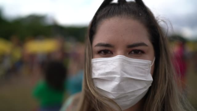 portrait of woman with facial mask in a public event - mask стоковые видео и кадры b-roll