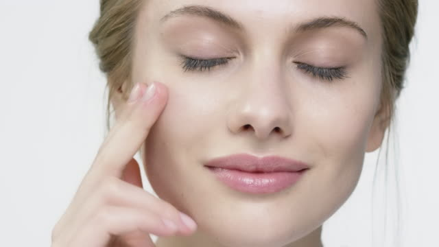 Portrait of woman with glossy lips applying cream