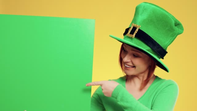 Portrait of woman with leprechaun's hat pointing at banner