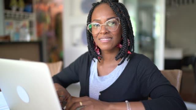 vídeos y material grabado en eventos de stock de retrato de la mujer que trabaja desde casa usando computadora portátil y teléfono inteligente - financial planning