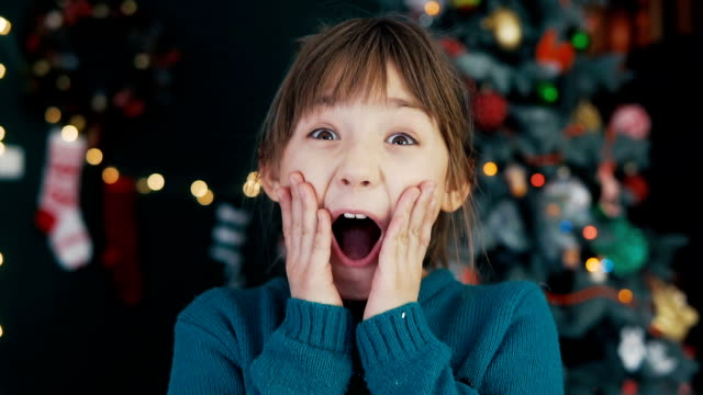 Portrait of Wondering Kid Girl Before Christmas Tree Portrait of a young surprized kid girl smiling before christmas tree background facial expression stock videos & royalty-free footage