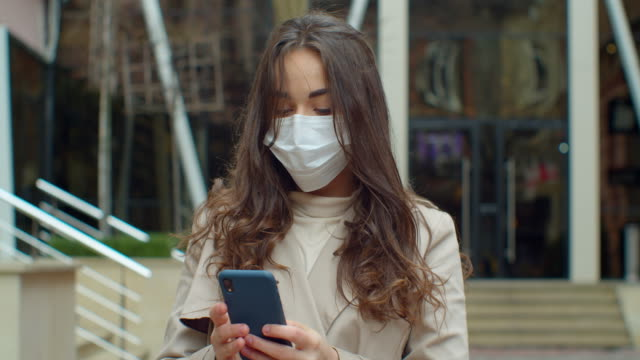 Portrait of worried woman standing on street in protective mask and using smartphone. Busy young girl reading news about coronavirus. Covid-19, pandemic, danger.