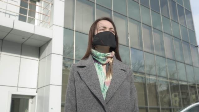 憂心忡忡的婦女的肖像站在街頭,戴著防護面具,使用智能手機。忙碌的年輕女孩閱讀有關冠狀病毒的新聞。科維德-19,大流行,危險。 - 亞洲中部 個影片檔及 b 捲影像