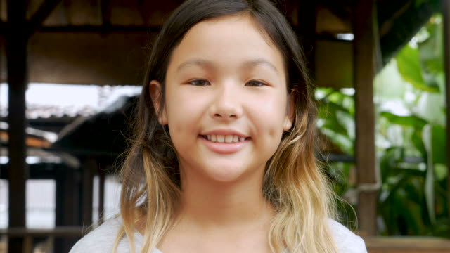 Portrait of young 11 - 12 year old cute happy Asian girl smiling