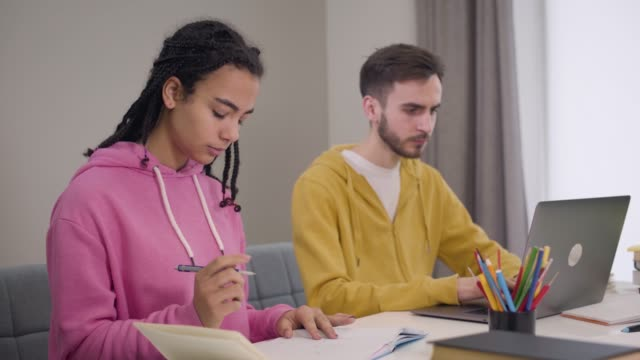 Portrait of young African American girl and Caucasian boy sitting at the table and studying. Man using laptop, woman writing down in workbook. Education, intelligence, lifestyle.