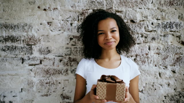 Portrait of young african american woman holding gift box and smiling into camera video