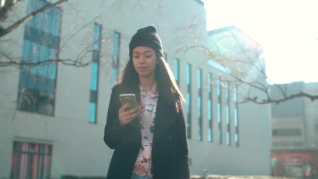 携帯電話を屋外で使う若いアフリカ系アメリカ人女性の肖像画。 ビデオ