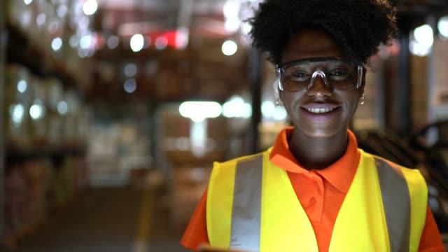 porträt eines jungen afrikanischen arbeiters mit digitalem tablet im lager - halle gebäude stock-videos und b-roll-filmmaterial
