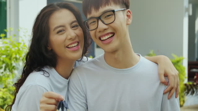 vídeos de stock e filmes b-roll de portrait of young asian couple in front of their house. new rich concept. holding house keys. - buy a house key