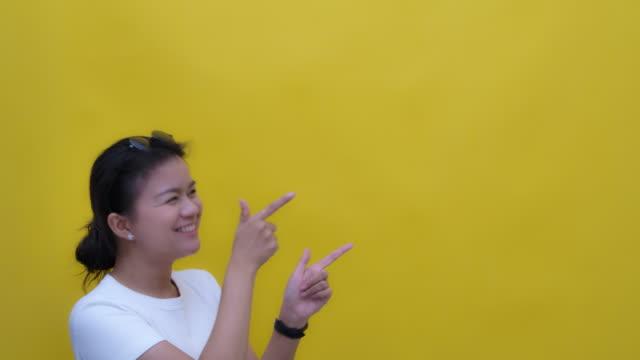 黄色の背景にコピースペース-手のジェスチャーを指して幸せな笑顔で若いアジア人のスローモーション写真 ビデオ