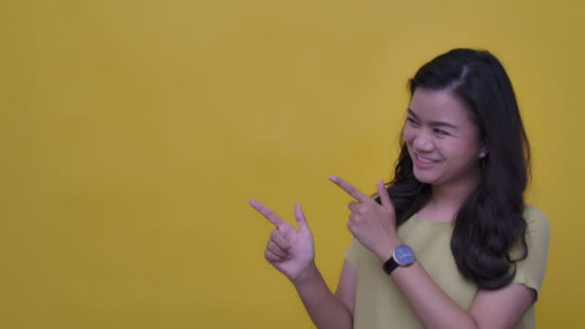SLO MO Portrait of young Asian with a happy smile pointing up at your logo- hand gesture on yellow background