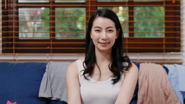 ホームリビングルームでソファーに座っている間にカメラを見ている若いアジアの女性の肖像 - 上半身点の映像素材/bロール
