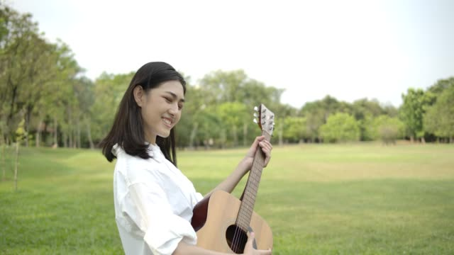 vídeos de stock e filmes b-roll de portrait of young attractive asian woman playing acoustic guitar in a summer park. woman with happy emotion concept. slow motion. - instrumental