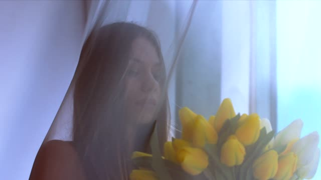 Portrait of young attractive Caucasian female smelling tulips and looking out the window. 60 FPS slow motion shot Portrait of young attractive Caucasian female smelling tulips and looking out the window. 60 FPS slow motion shot charming stock videos & royalty-free footage