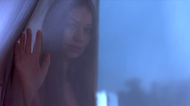 Portrait of young attractive Caucasian female walking near the window, looking into camera video