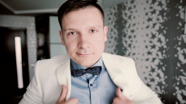 Portrait of young attractive man looking at camera and putting in order bow tie. Showman in white sit getting ready video