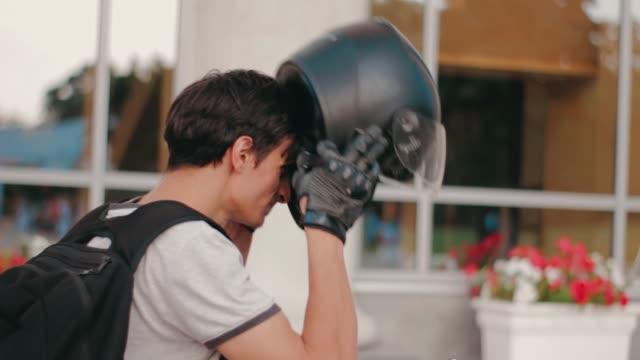 vídeos de stock e filmes b-roll de portrait of young attractive motorcyclist with black helmet on street. man motorcycle biker - helmet motorbike