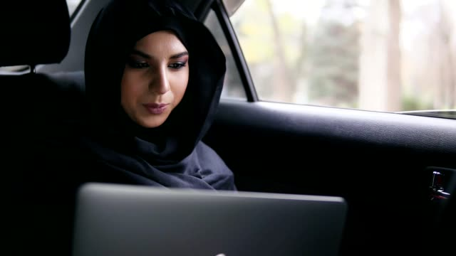 portrait of young attractive muslim woman in hijab sitting on the back seat in taxi and using her laptop. slowmotion shot - arab стоковые видео и кадры b-roll
