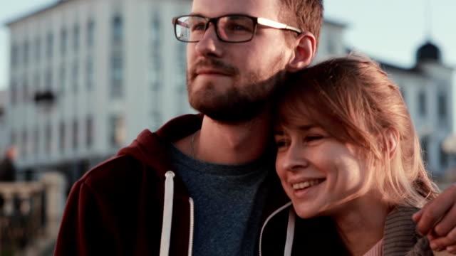 stockvideo's en b-roll-footage met portret van jonge mooie paar permanent in het centrum van de stad en op zoek naar opzij. gelukkig man en vrouw knuffelen op zonsondergang - sober leven