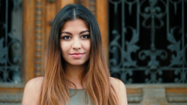 Portrait of young beautiful girl smiling outdoor. Woman with oriental face and stylish ombre dyed long haistyle. Street style. Slow motion. 4k video