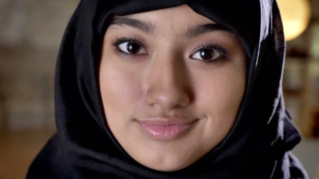 portrait of young beautiful muslim women in hijab looking in camera, smiling - vicino video stock e b–roll