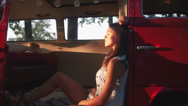 Portrait of young beautiful stylish woman in hippie retro bus in forest during sunset video
