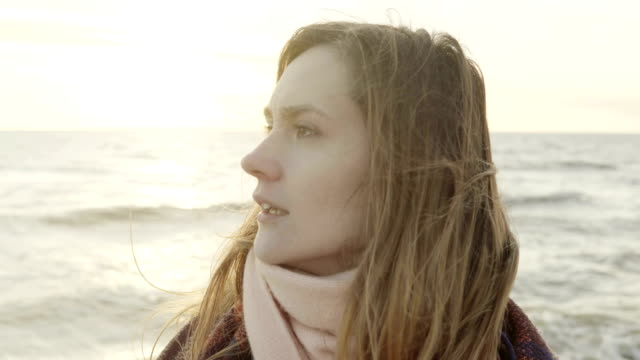 Portrait of young beautiful woman looking into the distance on the shore of sea. Female standing on beach in cold day video