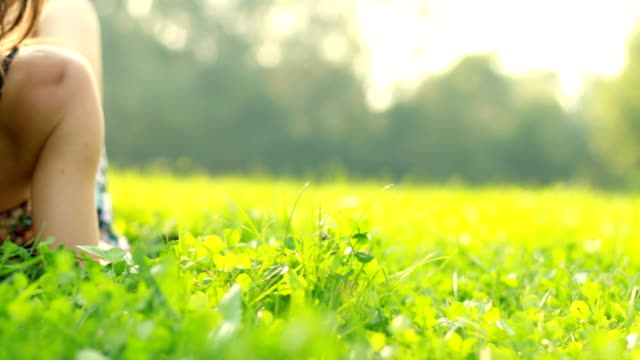 Portrait of young beautiful woman lying on grass, dolly shot video