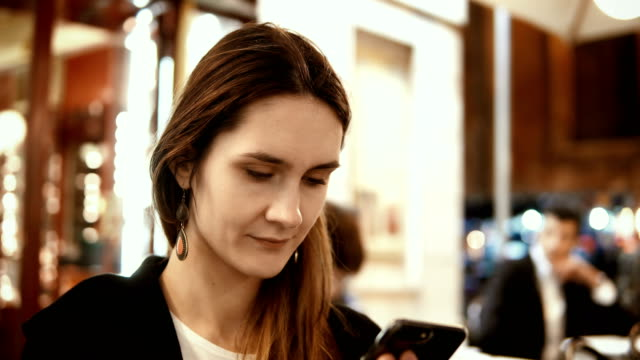 Portrait of young beautiful woman sitting in the city centre in the evening and using the smartphone in cafe video