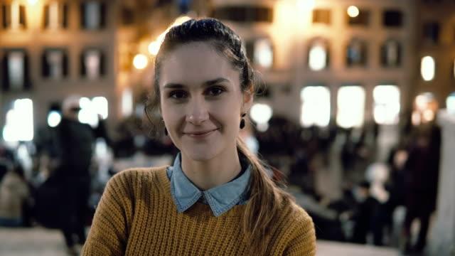 vídeos de stock, filmes e b-roll de retrato de uma jovem mulher bonita em pé no centro da cidade na noite. rapariga estudante olha para a câmera, sorrindo - camera