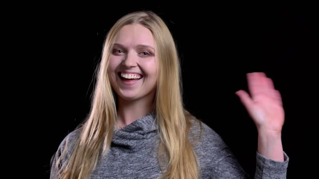portrait of young blonde straight-haired model waving hand gladly to greet somebody on black background. - occhiata laterale video stock e b–roll