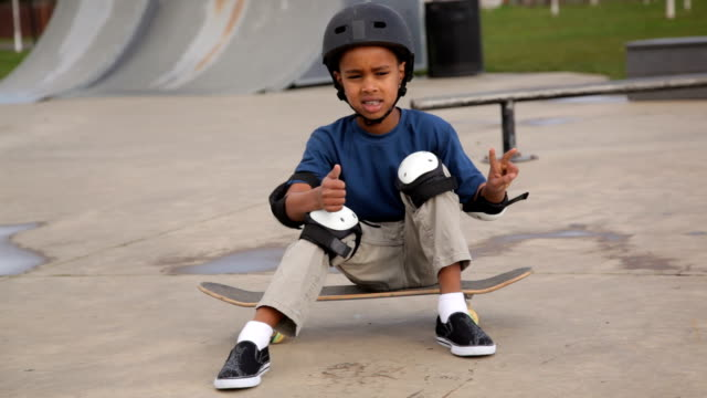 Portrait of young boy sitting on skateboard at skate park video
