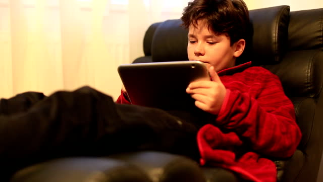portrait of young boy using digital tablet at home - solo un bambino maschio video stock e b–roll