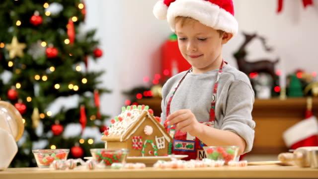 porträt eines jungen mit weihnachten lebkuchenhaus - lebkuchenhaus stock-videos und b-roll-filmmaterial