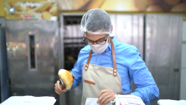 vídeos de stock e filmes b-roll de portrait of young business man owner with face mask at bakery - supermarket worker