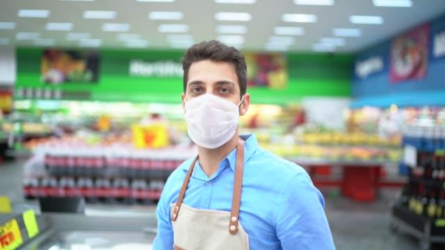 vídeos de stock e filmes b-roll de portrait of young business man owner with face mask at supermarket - supermarket worker