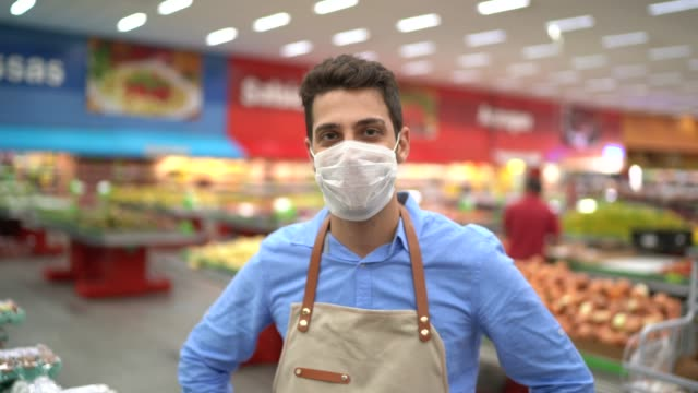 Portrait of young business man owner with face mask at supermarket video