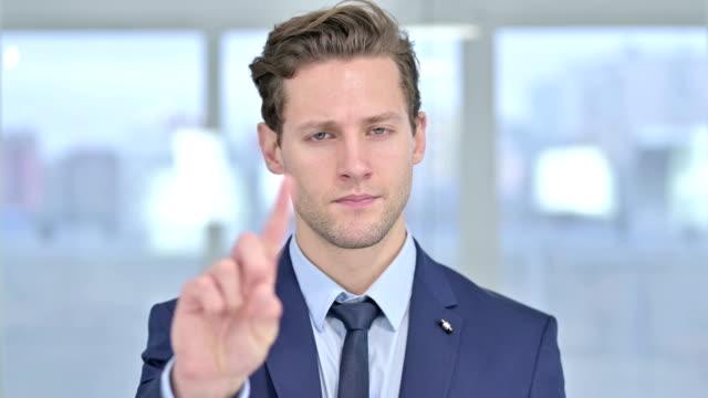 portrait of young  businessman saying no with finger sign - negacja filmów i materiałów b-roll
