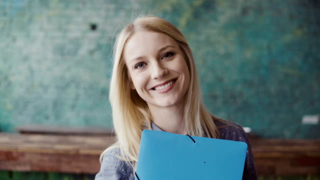 Portrait of young caucasian blonde woman looking at camera and smiling at modern office. Successful employee at work