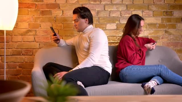 porträt des kaukasischen pärchen sitzen rücken an rücken auf sofa mit smartphones in die atmosphäre zu hause. - rücken an rücken stock-videos und b-roll-filmmaterial