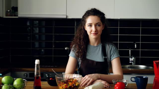 若い白人のエグゼクティブ シェフ エプロン軽く広々 としたキッチン、笑みを浮かべて、静かで、肯定的なカメラ目線でテーブルに座っている女性の肖像画 - 映画用カメラ点の映像素材/bロール