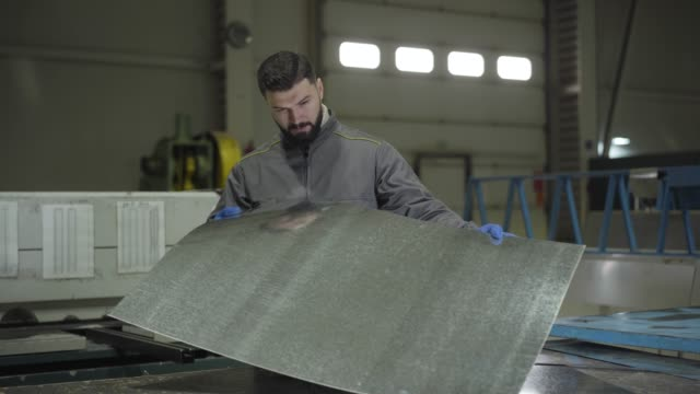 Portrait of young Caucasian foreman checking steel metal sheet. Handsome man in working gloves holding ready production on production site. Steel plant, manufacturing, metal production. Portrait of young Caucasian foreman checking steel metal sheet. Handsome man in working gloves holding ready production on production site. Steel plant, manufacturing, metal production. production line worker stock videos & royalty-free footage