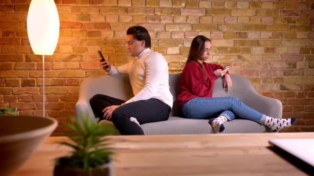 porträt des jungen kaukasischen freunde sitzen rücken an rücken auf sofa mit smartphones in die atmosphäre zu hause. - rücken an rücken stock-videos und b-roll-filmmaterial