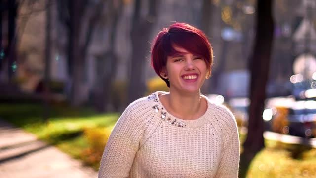 stockvideo's en b-roll-footage met portret van jonge kaukasische roze harige meisje met armen gekruist glimlachend nederig en gelukkig in de camera in het herfst park. - roze haar