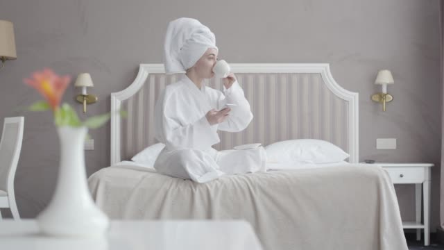 Portrait of young Caucasian woman in white bathrobe and hair towel drinking coffee and using social media in the morning. Relaxed girl sitting on bed in hotel room. Tourism, leisure, lifestyle.