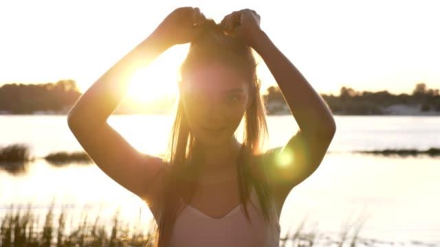 stockvideo's en b-roll-footage met portret van jonge charmante vrouw die in de camera, het aanraken van haar paardenstaart en glimlachend, lens flare, rivier en natuur achtergrond - paardenstaart haar naar achteren